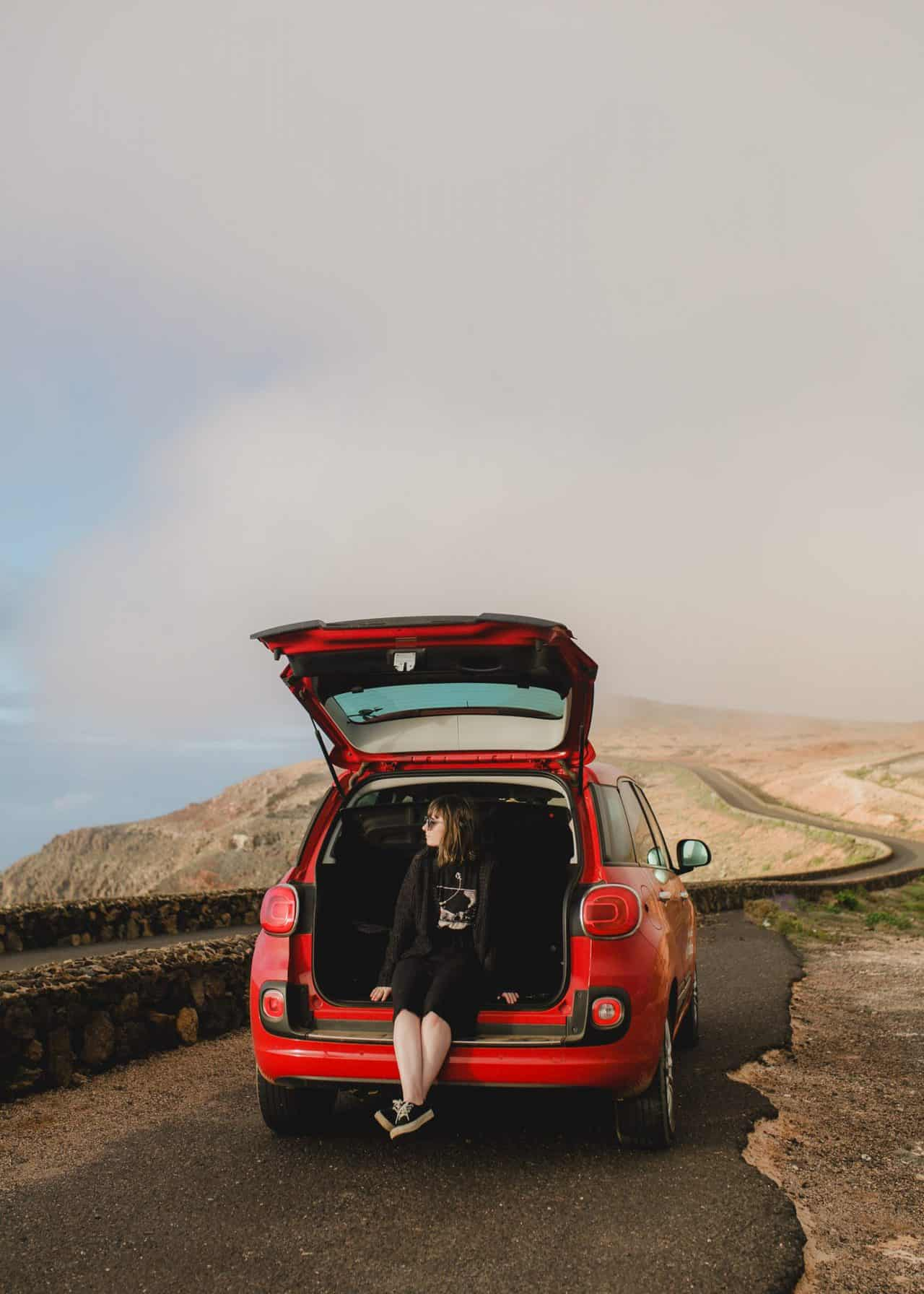 top 3 trips of 2018. girls sitting in boot of car on remote road in the mist.