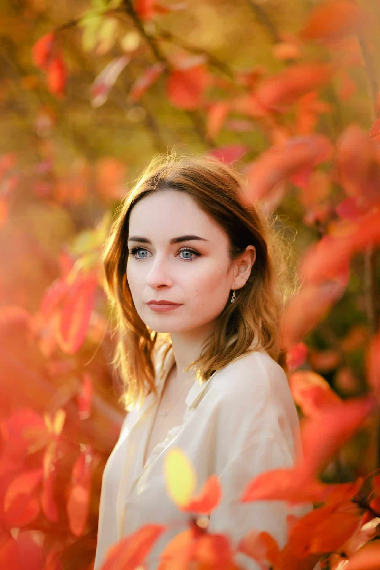 portrait of a girl wearing a silk shirt standing amongst autumn leaves. how to pose for photos