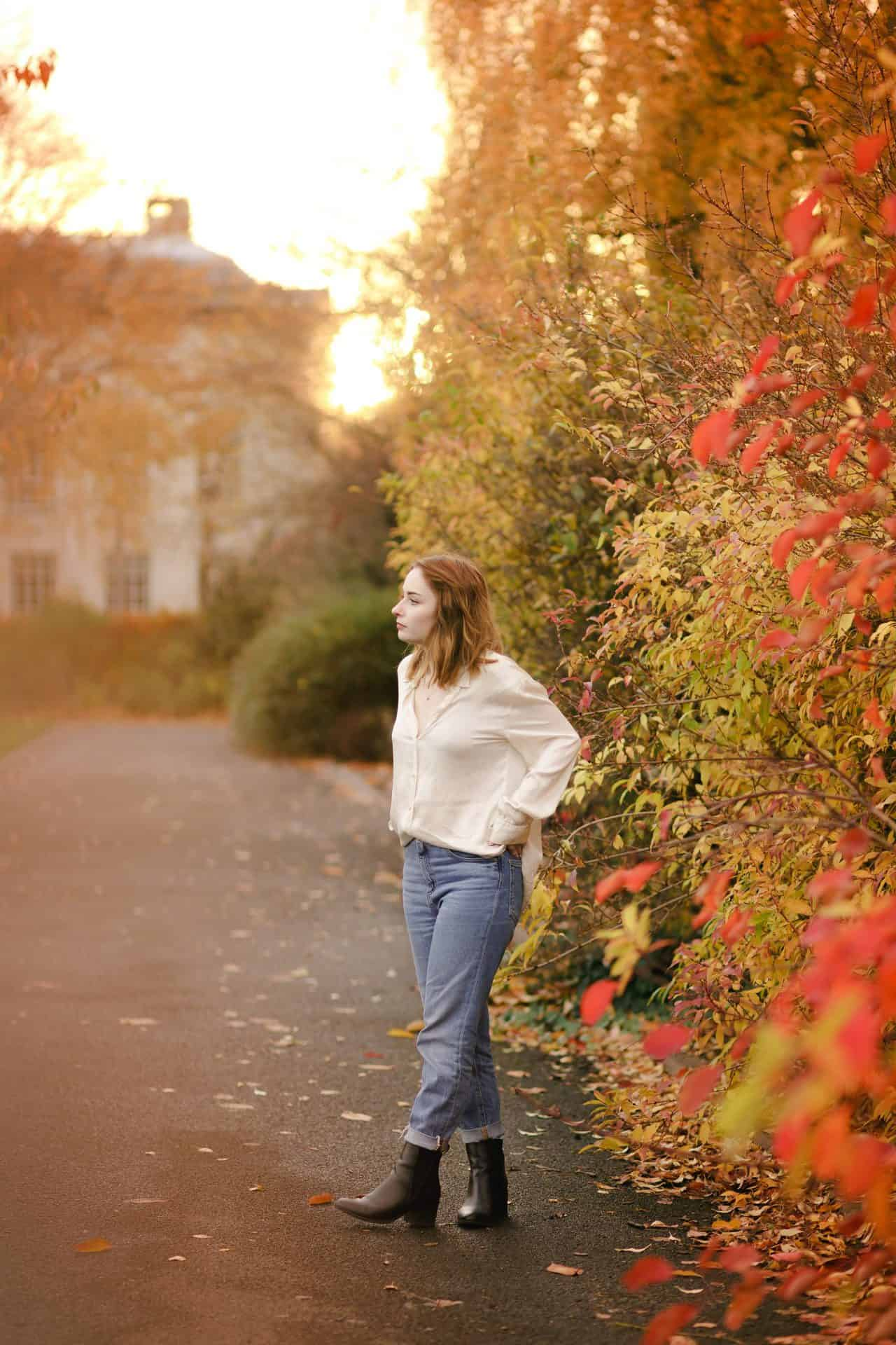 full length outfit photo of a girl wearing a silk shirt standing amongst autumn leaves. how to pose for photos
