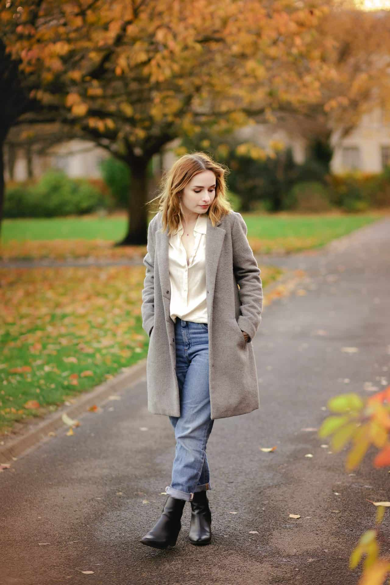 full length outfit photo of a girl wearing a cream silk shirt, blue jeans and grey longline coat standing amongst autumn leaves. how to pose for photos