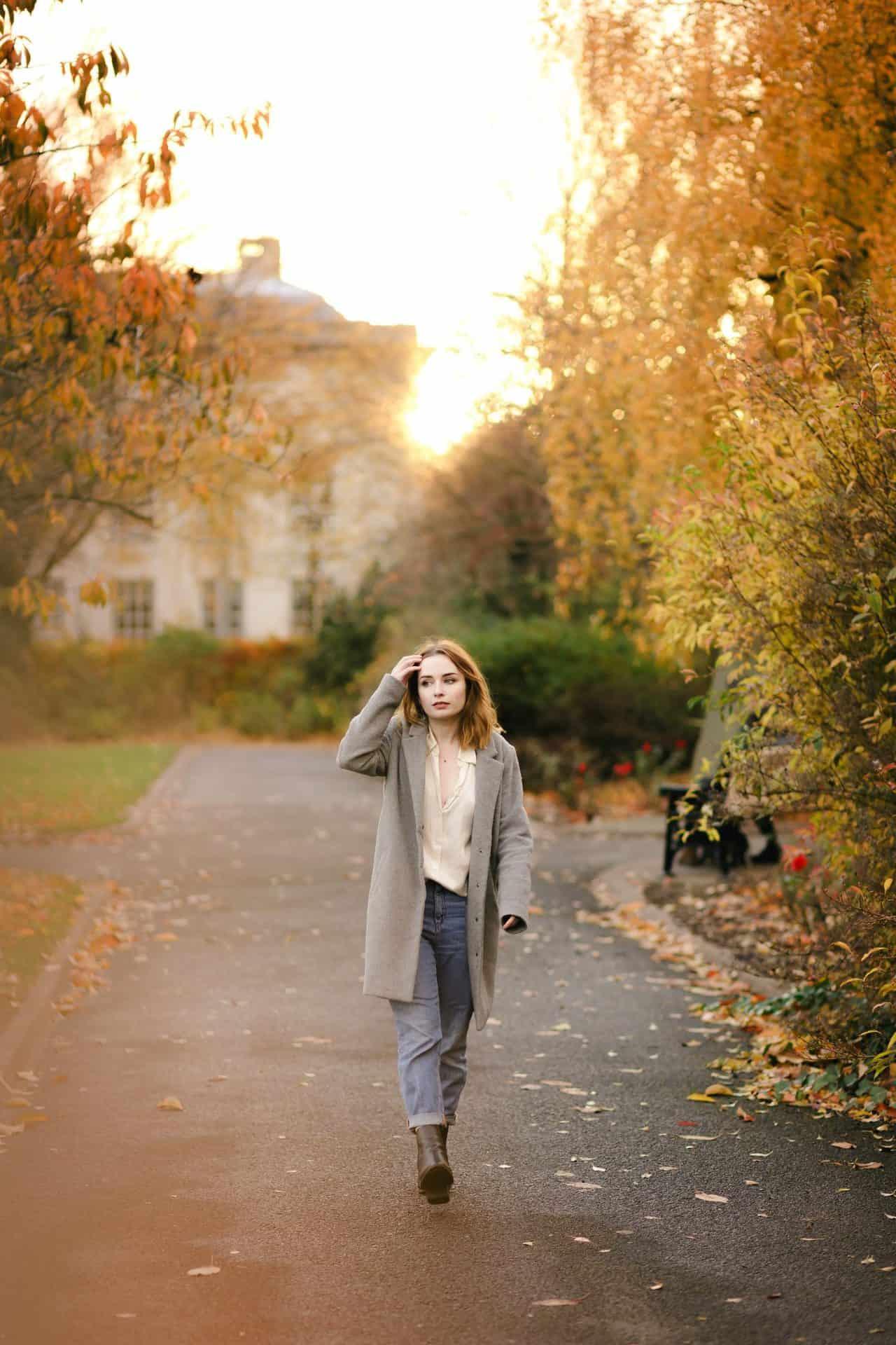 full length photo of a girl wearing a silk shirt and jeans standing amongst autumn leaves. how to pose for photos