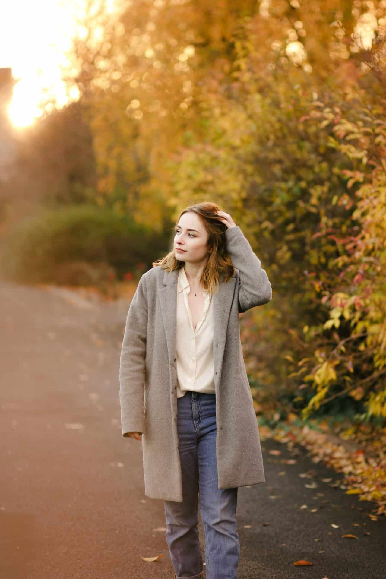 full length outfit photo of a girl wearing a silk shirt, jeans and coat standing amongst autumn leaves. how to pose for photos