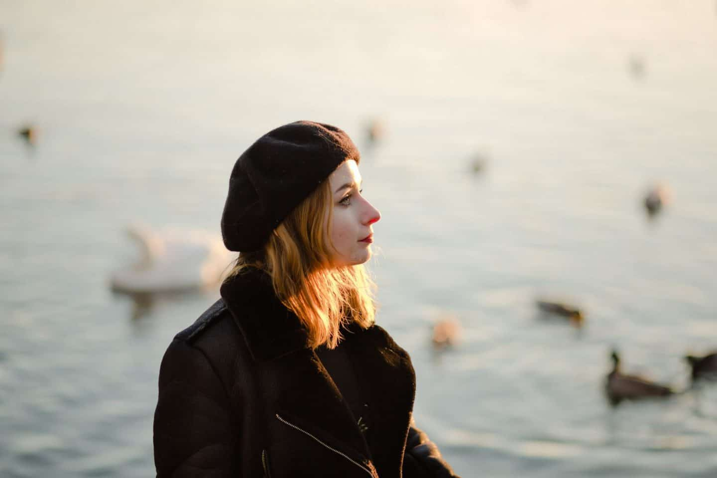 girl in sunset light wearing a beret and a faux shearling aviator jacket