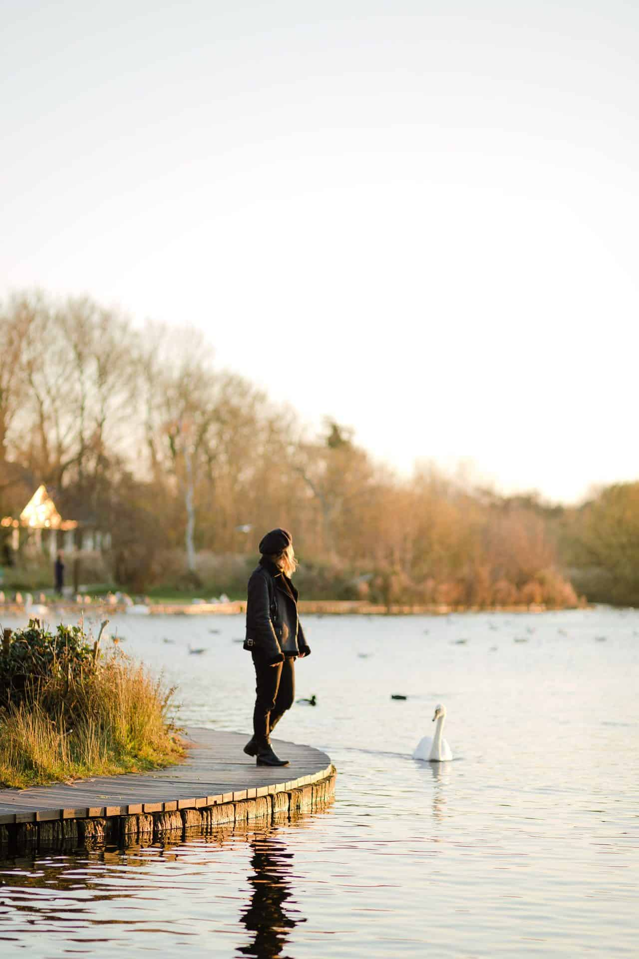 girl in sunset light stood by a lake wearing a beret and a faux shearling aviator jacket