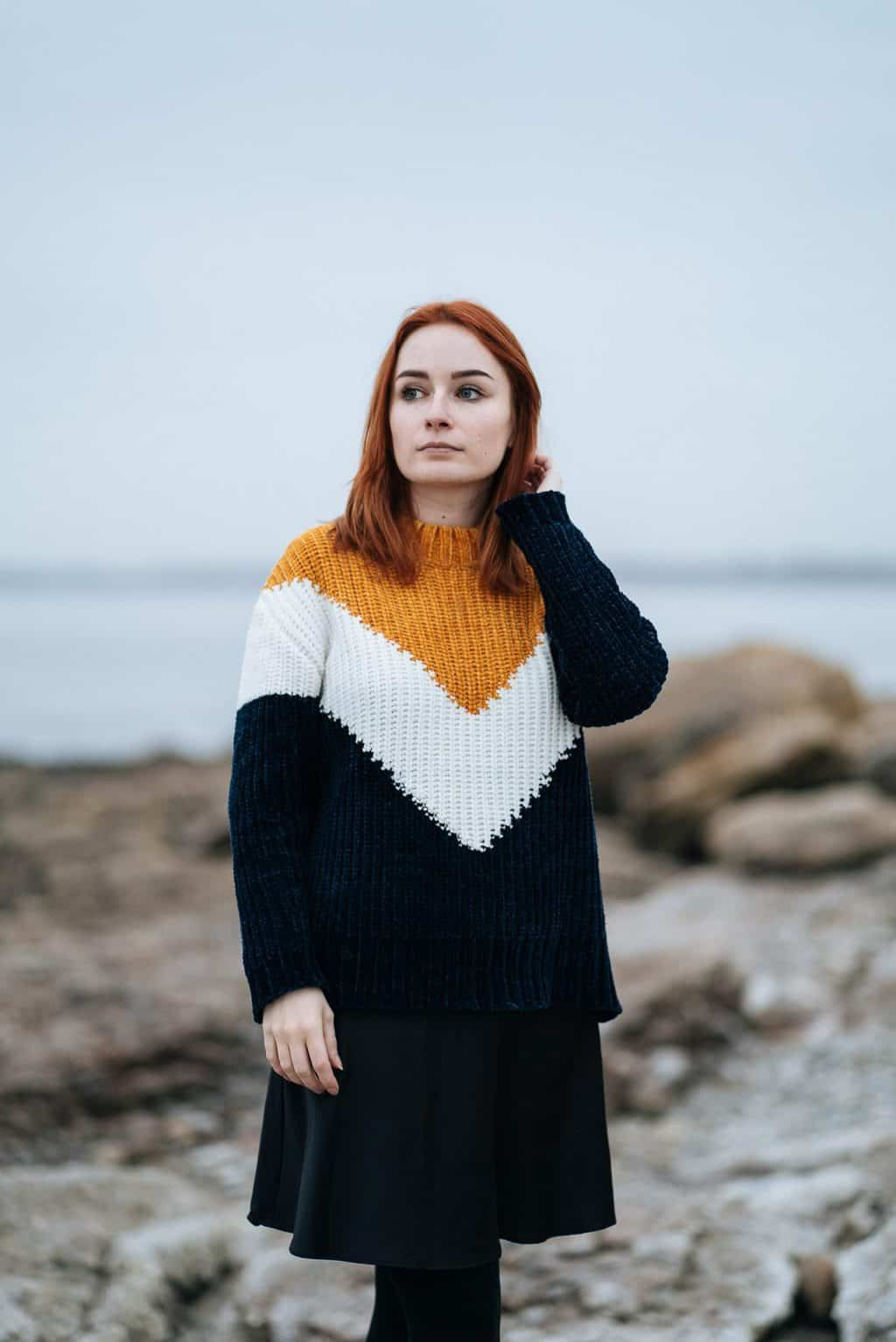 girl in striped chenille jumper standing on a rocky beach. Sustainable fashion purchase